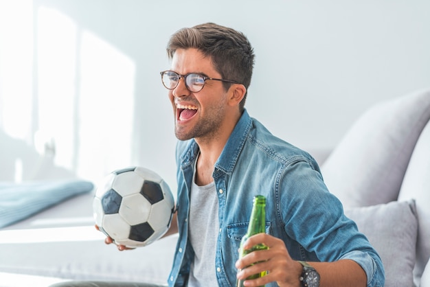 Fanatic football fan man watching soccer game on tv celebrating