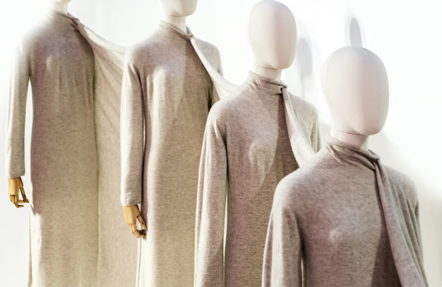 Fancy clothing on mannequins in a fashion store.