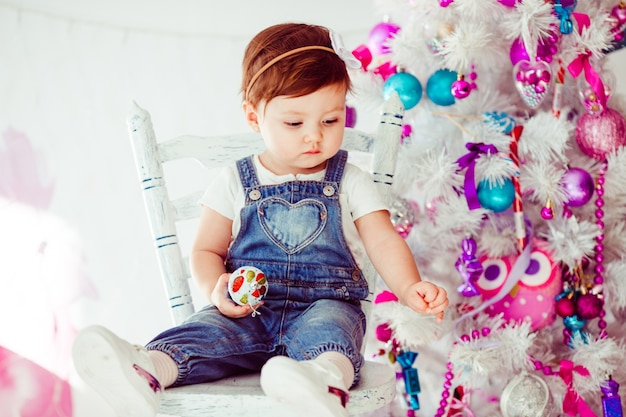 Fancy dressed little girl looks at something on christmas tree