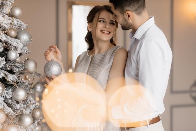 Нарядно одетые мужчина и женщина в серебряном платье обнимают друг друга нежно стоя перед елкой
