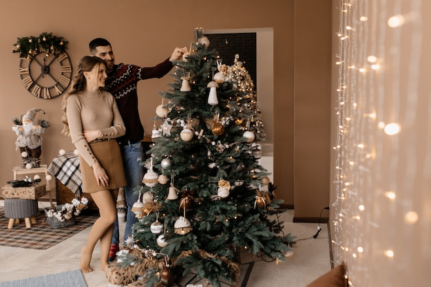 Fancy dressed man and woman in silver gown hug each other tender standing before a christmas tree