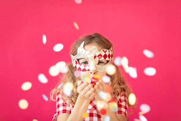 카니발 마디 그라 휴가 개념에서 재미 핑크 bakground 행복 한 아이에 대 한 색종이 불고 멋진 소녀
