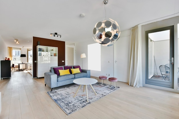 Fancy lamp hanging on ceiling over stylish furniture in spacious living room in modern flat