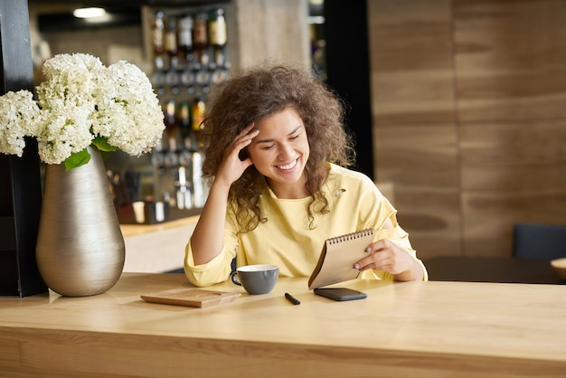 Fancy laughing young girl sitting on wooden table keeping blocknote.