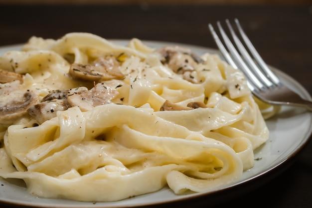 Fancy organic fetuccine pasta with creamy alfredo mushroom sauce. rustic plate and dark surface.