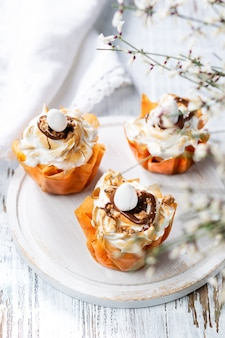 Fancy phyllo dough cups with meringue and melted chocolate close up on a plate.