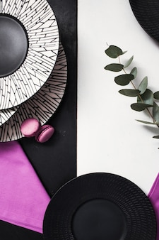Fancy plates on black and white background. creative restaurant table setting with flowers and purple color accents