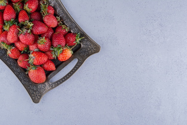 Fancy platter of juicy strawberries on marble background. high quality photo