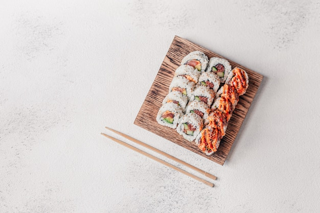 Необычные суши роллы подают на деревянной доске и палочками.