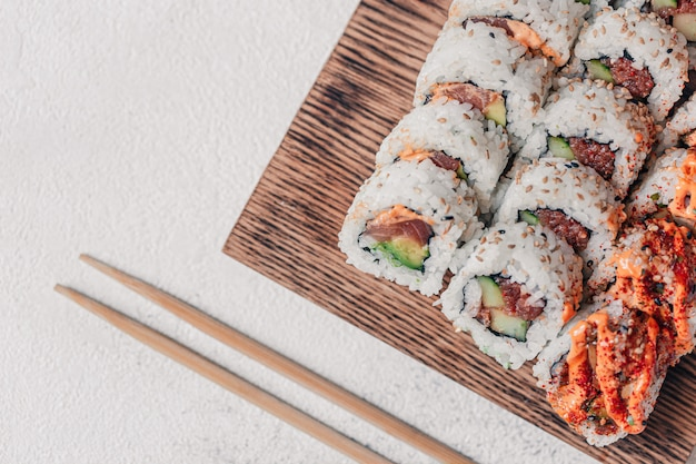 Fancy sushi rolls serving on a wooden board and a chop sticks.