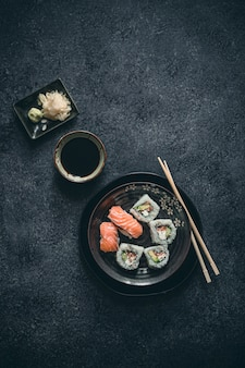Fancy sushi rolls with wasabi, ginger and soy sauce on black surface.