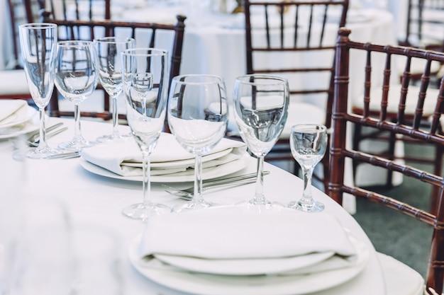 レストラン、豪華なインテリアの背景にナプキングラスとディナーに設定された豪華なテーブル