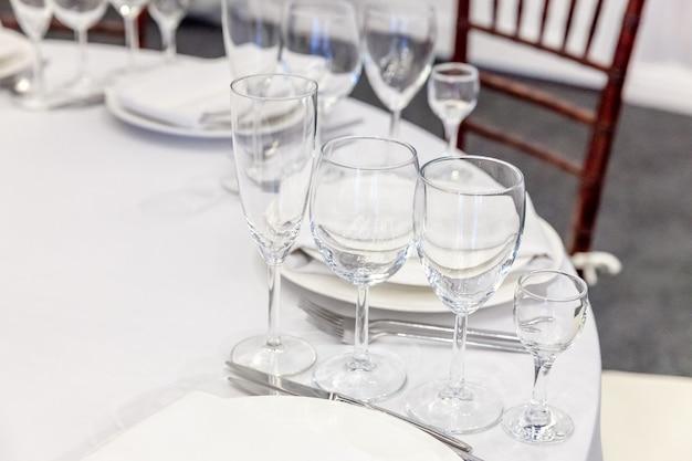 レストランでナプキングラスとディナーにセットされた豪華なテーブル、豪華なインテリアテーブル。結婚式の優雅な宴会の装飾と白いテーブルクロステーブルのケータリングサービスによって手配された食品のアイテム。