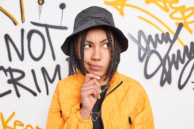 Fancy thoughtful teenage girl with braids holds chin and looks aside wears trendy black hat yellow jacket belongs to street gang poses against graffit wall