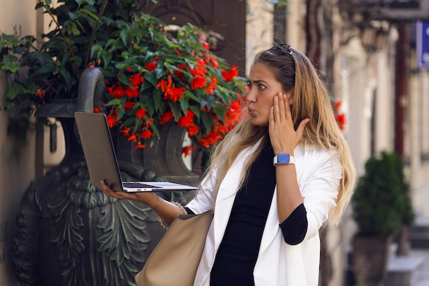 Fancy woman in fashionable clothes looking in her laptop and worries about some news. puts her hand on the cheek. watch on the wrist, purse hanging on the shoulder. standing by red flowers