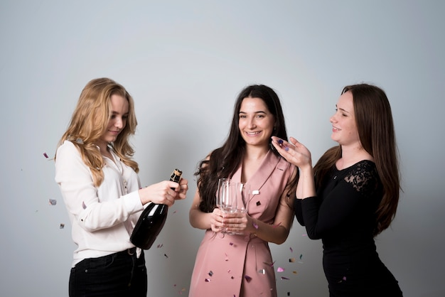 Fancy women opening bottle of champagne having party