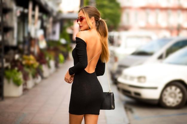 열린 섹시한 뒤와 긴 소매를 가진 검은 드레스를 입고 하루에 도시를 걷는 멋진 젊은 여성. 어깨에 지갑. 헤어 스타일에 금발 머리. 현대 메이크업과 안경. 부드럽고 부드러운 피부