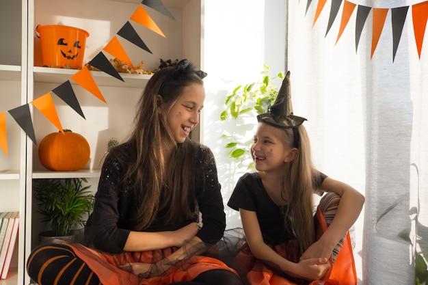 ハロウィーンの魔女の衣装を着た10歳と7歳のファニーガールズ姉妹が休日を祝う
