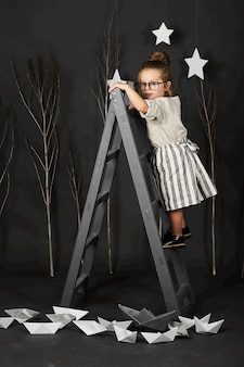 Fanny little girl with glasses on grey background with star and ladder