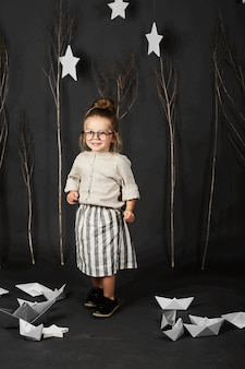 Fanny little girl with glasses on grey background with stars, trees and paper boats
