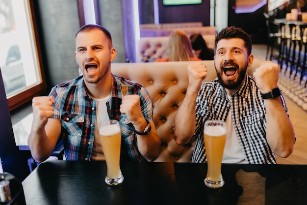 Fans two young men in plaid shirt at bar raised their hands with glasses of beer up and screaming, emotions from exciting game on tv