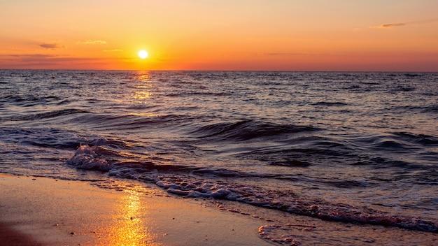 夏の日の波状の海に沈む幻想的なカラフルな夕日