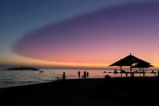 夕暮れ時のビーチの空と海岸の人々のシルエットの幻想的な色