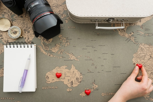 Fantastic composition with hand placing hearts on map