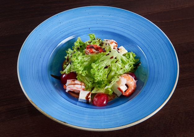 Fantastic delicious shrimp salad with feta cheese and grapes served in a big blue rustic plate top view