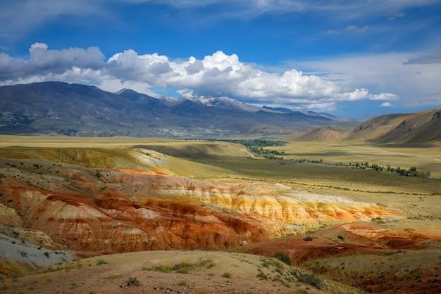 화창한 날에 환상적인 황량한 산 풍경입니다. 흰 구름과 푸른 하늘 아래 다채로운 바위입니다.