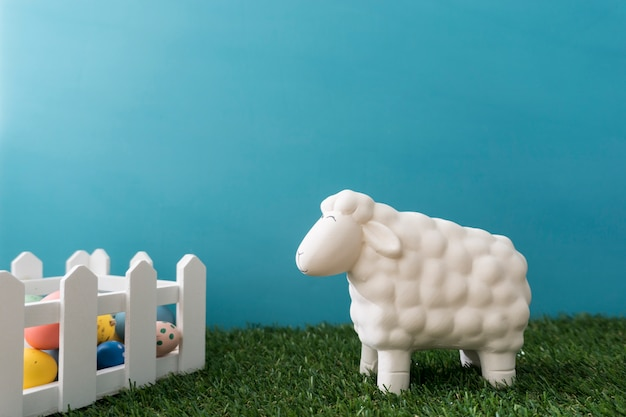 Fantastic easter composition with sheep next to wooden fence
