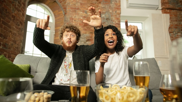 Fantastic. excited couple, friends watching sport match, championship at home. multiethnic friends, fans cheering for favourite sport team