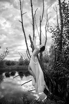 Фантастическая фея красивая женщина в белом длинном платье на старом сухом дереве. девушка-принцесса в болоте. сексуальная девушка фотомодели позирует на дереве на озере. сказка