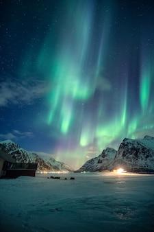 幻想的な緑のオーロラ、ノルウェーのロフォーテン諸島の冬の夜空に雪に覆われた山に星が輝くオーロラ