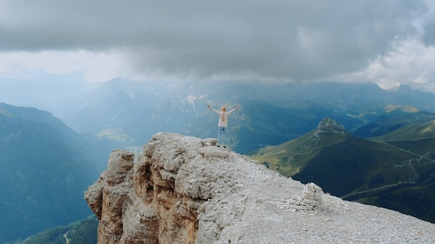 Fantastic landscape of mountain rocks and woman standing on the top with outstretched hands