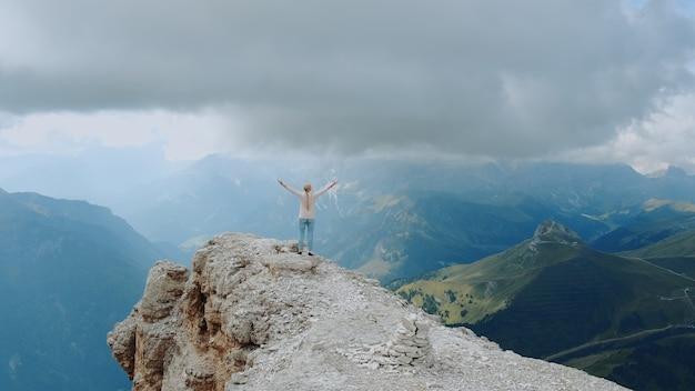 Фантастический пейзаж горных скал и женщины, стоящей на вершине с протянутыми руками