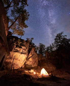 Fantastic landscape at summer night. brightly burning small campfire in canyon amid huge steep rock formation under clear dark starry sky. tourism, safety, climbing, hiking and traveling concept.