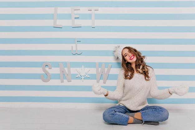 座って楽しんでいる幻想的ないたずらな白いモデル。若い女性が笑って「雪を降らせて」の碑文にポーズをとる