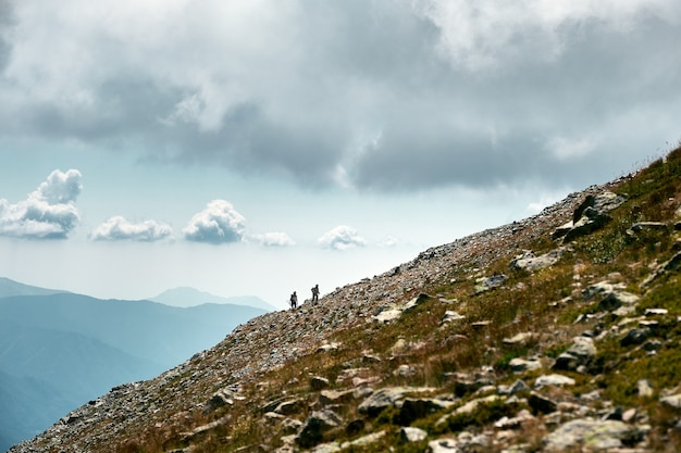 Fantastico scatto di escursionisti in lontananza che scalano un pendio di una montagna in costa azzurra