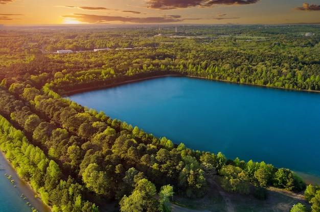 Фантастическая летняя панорама озера с воздуха между деревьями в лесу