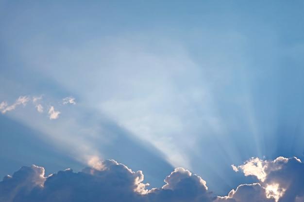 ふわふわの雲の切れ間から輝く幻想的な太陽光線