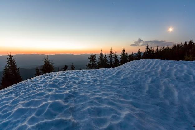 冬の山の夜の素晴らしい景色。雪に覆われた丘の背後にある松の木の暗い緑のトップと地平線上のオレンジ色の輝きと静かな青い空の最初の明るい星。自然の息をのむような美しさ。