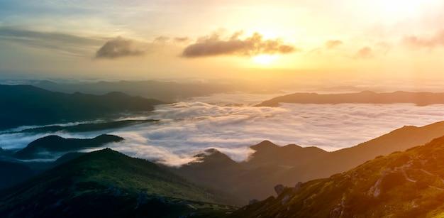 霧の地平線に伸びる雪雲のような低い白いふくらんでいる山の谷の素晴らしい景色