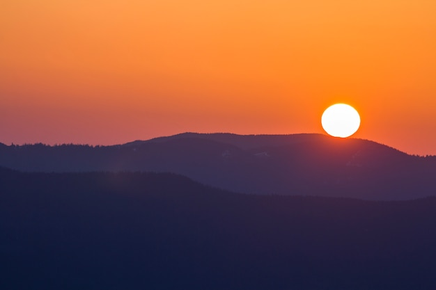 Фантастический широкий панорамный вид большого яркого белого солнца в драматическом оранжевом небе над темно-фиолетовой горной цепью на закате или восходе солнца в карпатах. красота и великолепие природы концепции.