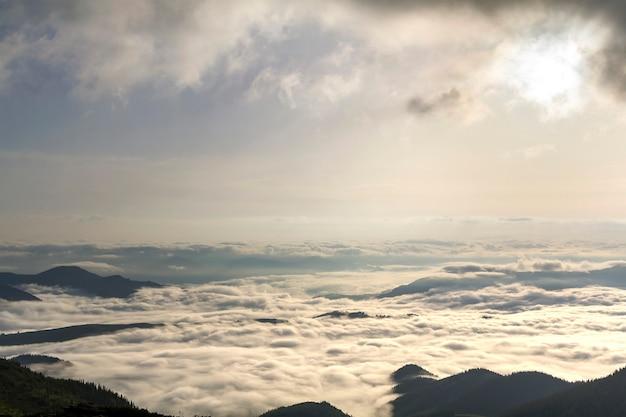 雪の雲のような白いふくらんでいる霧と夜明けの明るい朝の曇り空の下で地平線に伸びる霧で満たされた山の谷の素晴らしい広い平面図。自然概念の美しさと壮大さ。