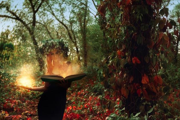 幻想的な若い魔女は、屋外の森の中で魔法の本によって想起させます