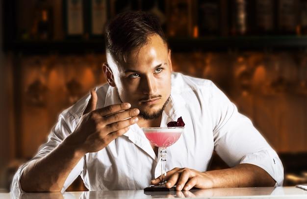 Сказочно обаятельный бармен наслаждается ароматом свежеприготовленного коктейля. смешанная техника