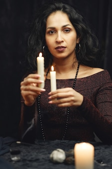 Fantasy beautiful gypsy girl. fortune teller woman reading future on magical tarot cards.