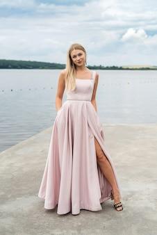 Fantasy charming woman in elegant ping evening dress relaxing near lake, summer time
