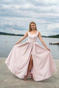 湖の近くでリラックスできるエレガントなpingイブニングドレスのファンタジー魅力的な女性、夏の時間